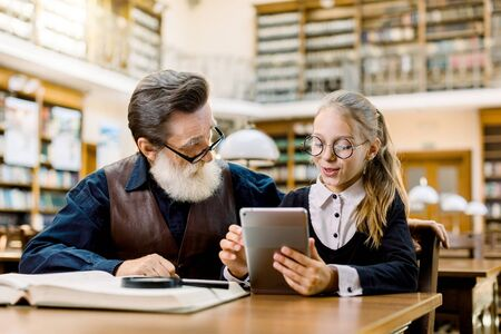 Senior man in vintage shirt and leather vest and little pretty girl granddaughter looking at a tablet, while sitting and studying together in library. Old book shelves on the background