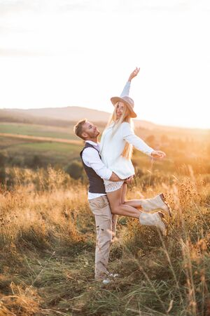Young couple wearing hipster boho indie style clothes, in love walking in countryside, man holds woman on hands, woman is happy and smiling. Sunny sunset field on background, warm summer day