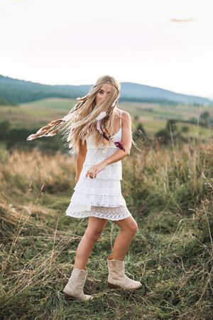 Beautiful young boho hippie girl in white dress at sunset, smiling and having fun. Feathers in hair, bohemia boho style Standard-Bild