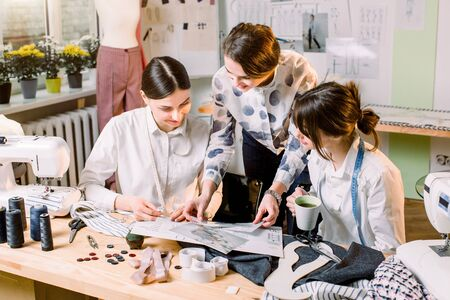Three attractive young fashion designers carefully creating new fashionable styles of pants. Dressmakers making clothes. Fashion, dressmaker, sewing concept