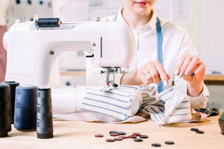 Cropped shot of woman sewing on machine in design studio. Young seamstress sews clothes. Workplace of tailor - sewing machine, rolls of thread, fabric, scissors. Focus on sewing machine.