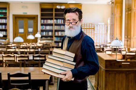 Portrait of confident elegant librarian of university professor teacher man, wearing stylish clothes, happy to share knowledge, holding stack of different books, standing in vintage library indoors Archivio Fotografico - 142224742