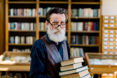 Portrait of handsome senior bearded retired man, librarian or teacher, choosing books in library, holding stack of books, looking at camera, book shelves on the background.