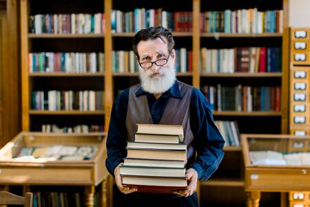 Portrait of positive smart old bearded man in dark shirt and leather vest, library worker, teacher, working in library, holding stack of books while standing over book shelves background.