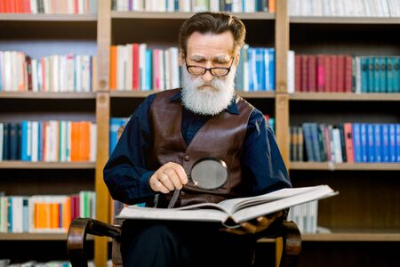 Senior bearded man in glasses, academic professor or teacher, sitting and reading an old book in the library, holding magnifying glass. Knowledge, learning and education concept.