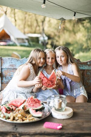 Three cute happy smiling girls, sisters, fiends, sitting at the table on vintage wooden bench and eating watermelon outdoors, in tent, stylish boho wigwam on background. Countryside summer holidays.