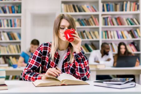 Pleasant smart Caucasian woman student reading book at university library and drinking coffee. Girl student reading book, preparing for test and exams. Multiethnic students studying on the background
