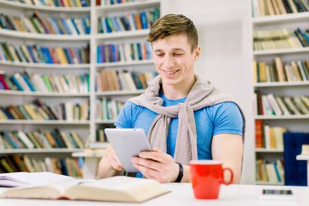 Smiling satisfied handsome young male student sitting in the library and searching information on i-pad during preparation for test, homework or exam. Smart education and digital technologies Stockfoto
