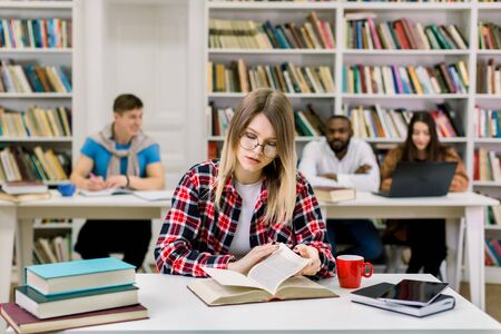 Portrait of a pretty young student girl studying at college library, sitting at the table and reading textbook. Multiethnic students studying together on the background. Preparation for exams Stockfoto