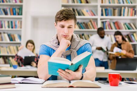 Smart confident young Caucasian man studying in library for test or exam, he is sitting at desk and reading a book, while his groupmates discussing on the background. Knowledge and learning concept