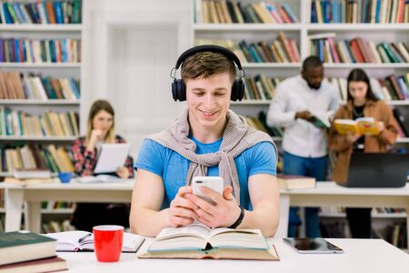 Portrait of funny smiling young man sitting at the table in library, enjoying favourite melodies in earphones from his phone playlist, having break during preparation for exams. Student life concept