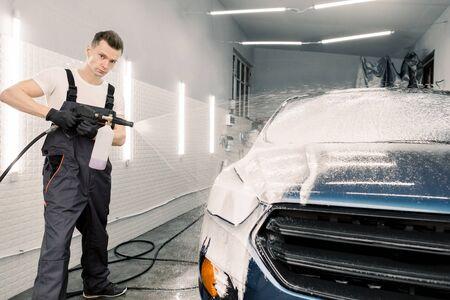 Caucasian man car wash worker is spraying cleaning foam to a modern blue car holding a high pressure washer. Modern car and foam washing 版權商用圖片