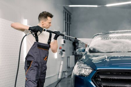 Cleaning car using high pressure water. Handsome young man worker washing modern blue car under high pressure water in car wash service