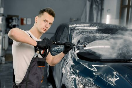 Young good-looking man worker washing luxury dark blue car on a car wash, looking at camera and holding high pressure water washer. Car wash concept