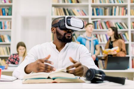 Young attractive African man with beard wearing casual white shirt, studying in library, using virtual reality goggles headset, flipping through book pages. Diverse students studying on the background