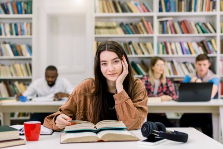 Young beautiful girl with straight long dark hair wearing in brown shirt, sitting at the table in library and preparing for test or exam, reading books. Girl posing on camera with smile