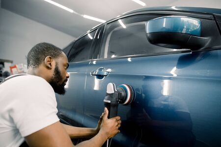 Young African man working at car detailing service, polishing blue car with polisher to eliminate contaminants from the surface of the car