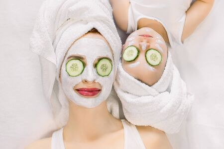 Mother and little daughter having spa procedures together. They are in white bath towels on head and with slices of cucumber on their eyes. Woman has white facial mask on her skin
