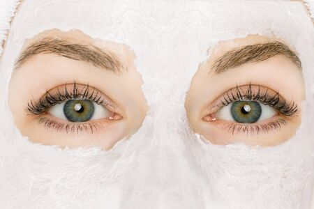 Close up macro image of beautiful female green gray eyes of young beautiful girl with natural eyebrows and makeup, looking at camera. Pretty woman getting facial mud mask, spa and cosmetology