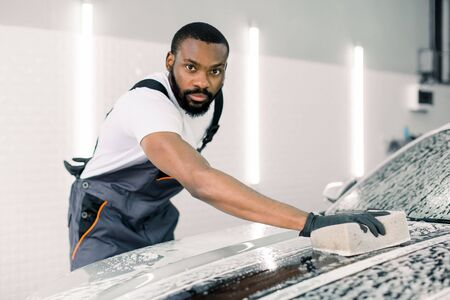 Professional handsome dark skinned man worker washing a soapy car hood with a beige sponge, posing and looking at camera. Car cleaning, detailing, wash service concept