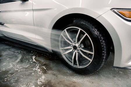 Washing a car by hand, car detailing. Close up image of the process of cleaning the car wheels with a water gun. Car rims wash using high pressure water. Detail of manual wheel cleaning concept.