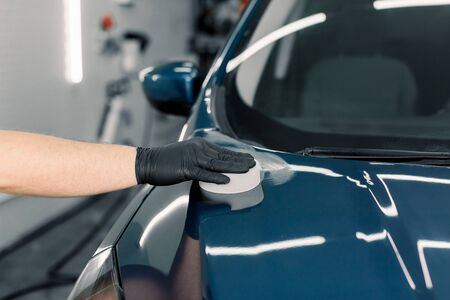 Cropped close up image of male hand in protective black glove, holding white sponge with solid carnauba wax, and polishing hood of luxury blue car at professional detailing workshop. Car detailing Фото со стока
