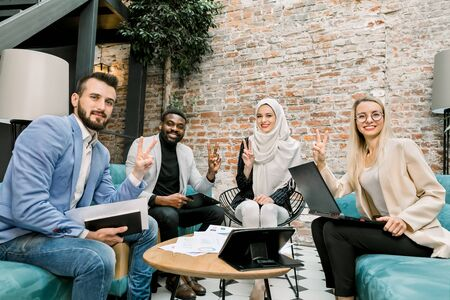 Happy cheerful multi-ethnic business team, two women and two men, showing victory hand sign looking at camera dn asmiling, while sitting on the sofas in the office over the brick wall background
