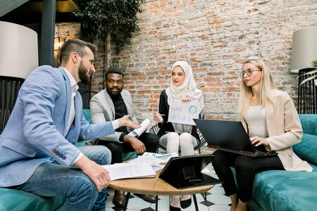 Multiethnic business people on the meeting in office. Arabian business lady in white hijab using financial document with graphs talking to her male and female partners about the results of research
