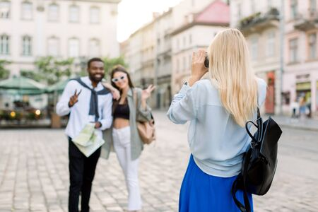 Summer holidays, technology and city travel concept. Back view of pretty Caucasian blond girl taking photo of two multiethnic friends, dark skinned man and Caucasian woman in the city