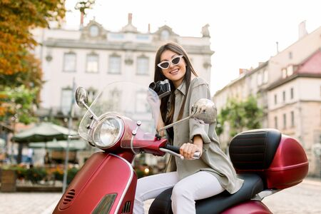 Young beautiful brunette woman in stylish casual wear and sunglasses, sitting on red motorbike scooter in the city street outdoors, posing on camera and smiling, old buildings on the background. Archivio Fotografico
