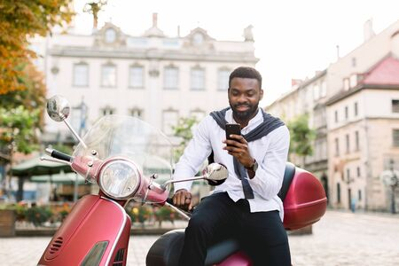 Portrait of smiling young bearded african american guy in smart casual wear using his smartphone, while sitting on the red scooter outdoors on the old city square. Urban lifestyle, business
