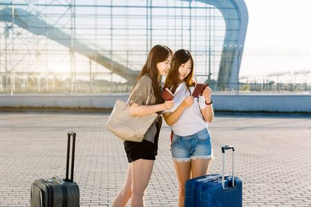 Two lovely happy young asian women in casual clothes, checking their passports and flight tickets, while standing near the modern airport gate with big suitcases. Joint trip, vacation concept