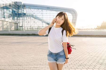 Pretty cheerful 25-aged asian brunette girl in jeans shorts and white t-shirt enjoying her conversation with friend on smartphone in front of modern airport building. Travel and technologies concept