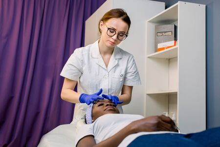 Young African American female getting a facial head massage. Pretty Caucasian woman massagist or cosmetologist doing facial massage. Spa, massage, skin care concept Foto de archivo