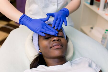 Relaxed Young African Woman Receiving Forehead Massage In Spa. Woman massagist in blue rubber gloves performing facial massage. Spa, massage concept Foto de archivo