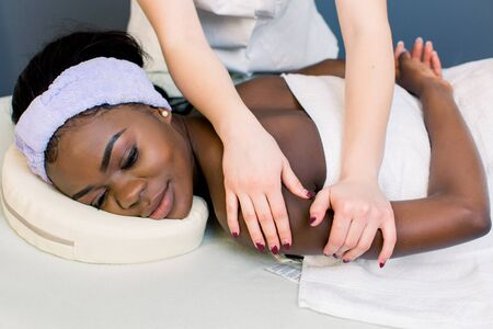 Attractive african girl having massage relaxing in spa salon. Closed eyes. Closeup of happy african woman receiving back massage at salon spa