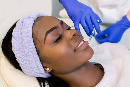 Plastic surgery. Young African woman getting cosmetic injection in lips. Side view of beautiful African woman making beauty injection for lips. Stok Fotoğraf