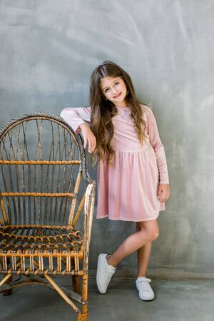 Cute baby girl 5-6 year old wearing stylish pink dress overgrey background. Looking at camera. Birthday party. Celebration.