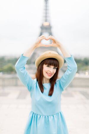 Elegant smiling young woman in blue dress and hat posing near the Eiffel tower at Trocadero view point in Paris, France, and making heart gesture sigh by her hands. Love with Paris, travel concept 版權商用圖片