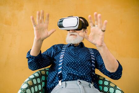 Elderly people and technologies. Handsome senior bearded man in stylish hipster clothes, sitting on the chair on yellow background and and enjoying film or game in augmented reality goggles.