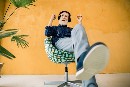 Full length portrait of handsome elderly bearded man, wearing stylish hipster clothes, relaxing in chair while listening his favourite music in headphones. Studio shot on yellow background