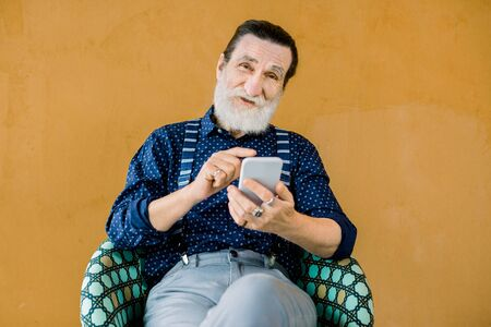 Portrait of pleasant senior smiling bearded man, wearing stylish shirt and pants, sitting on the yellow background and using the phone apps or social networks. Elderly man vs digital technologies
