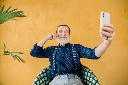Happy cheerful handsome mature hipster man with gray beard, wearing stylish trendy clothes, holding his smartphone for making selfie photo, sitting on isolated yellow background with palm tree