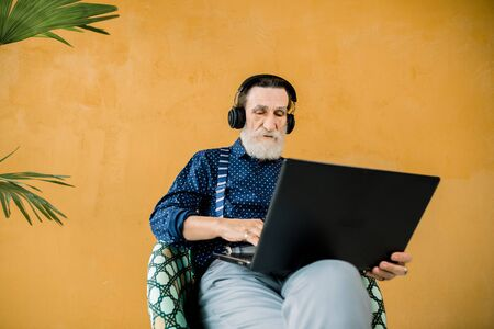 Studio shot of handsome concentrated senior man in stylish clothes, wearing earphones, sitting in the chair and using laptop computer. Senior people and digital technologies