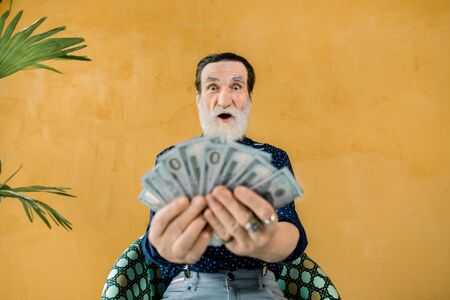 Funny photo of cheerful excited gray-bearded man holding a lot of paper money in hands, and posing on camera, sitting on the chair in studio on yellow bright background Banque d'images