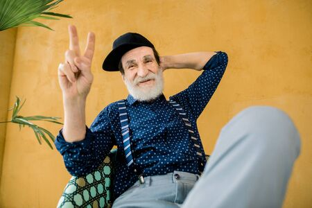 Attractive satisfied confident stylish senior bearded man in trendy clothes and black hipster cap, posing on camera with one hand behind his head and another showing victory sign gesture Banque d'images