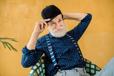 Handsome stylish senior man in dark blue shirt, suspenders and black hipster cap posing in studio, sitting in front of yellow wall. Stylish fashionable elderly man on yellow background Banque d'images