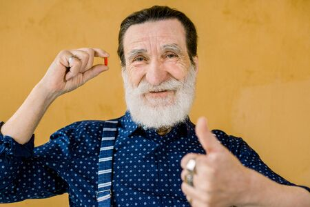 Senior handsome bearded smiling man, wearing stylish clothes, posing against yellow background, holding red pill in one hand and showing his thumb up. Elderly age and medicine concept