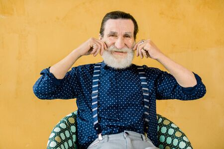 Portrait of smiling elderly gray-haired bearded man in dark blue shirt and suspenders, posing isolated on yellow studio background, touching his mustache. People emotions and lifestyle concept.