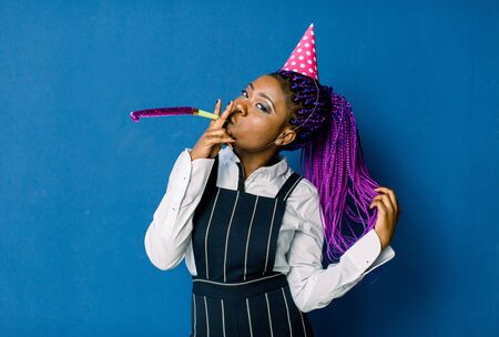 celebration, friends, bachelorette party, birthday concept - smiling African American woman wearing pink party hat and blowing favor horn